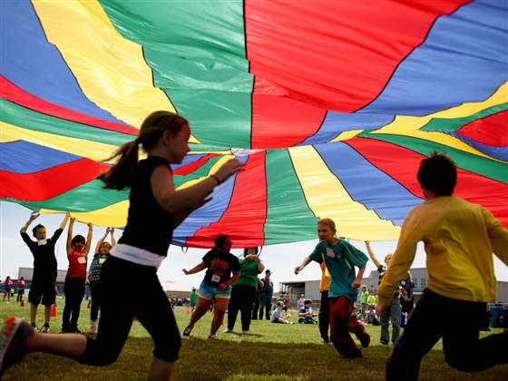 Aaron Marineau / The Hutchinson News via AP fileNickerson Elementary School third-graders dash under a rainbow colored tarp before it falls back down on them in Hutchinson, Kan., on April 25, 2013.